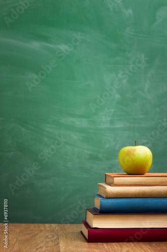 School books with apple on desk - 69378110