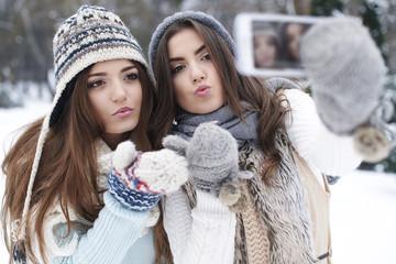 Best friends taking selfie in winter