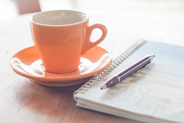 Cup of coffee with pen and spiral notebook