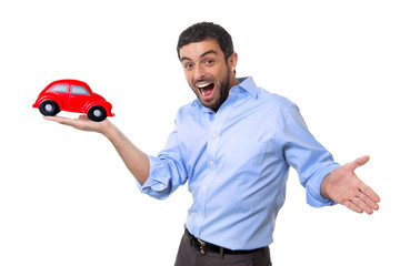 young happy attractive man pointing big red toy car on his hand