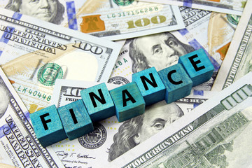 word finance on wooden cubes on american dollars background