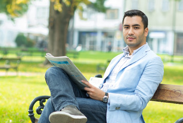 Young businessman sitting on bench and reading newspaper