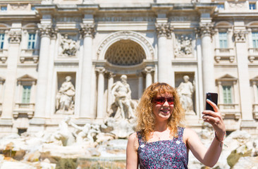 Selfie of a young tourist on the background of Trevi Fountain