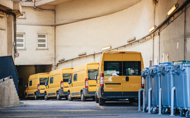 Yellow delivery vans trucks distribution in warehouse center