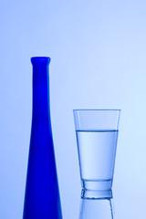 Wasserglas mit blauer Flasche