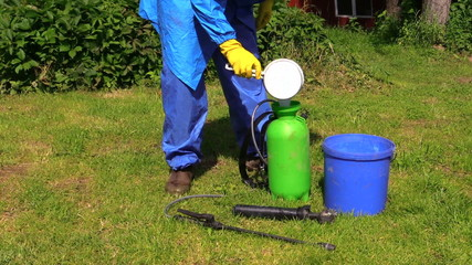 man with chemistryproof clothing hand pour fertilizer to spray