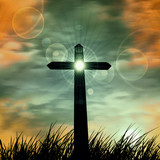 cross in a grass with sunset sky background