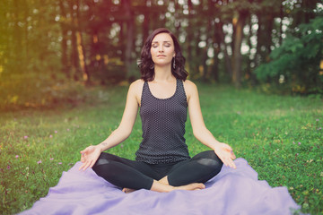 Woman meditating in a green field with trees