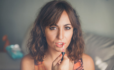 Attractive woman applying lipstick or lip gloss