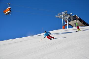 Skifahrer auf Piste und Sessellift