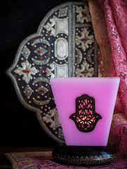 Moroccan candle with charm hamsa, a mirror and a cloth