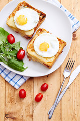 Croque monsieur with eggs and salad on vintage table