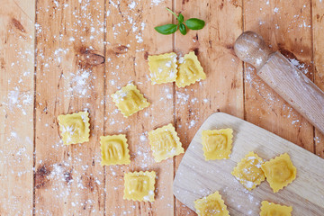 Ravioli pasta on vintage wooden table and flour