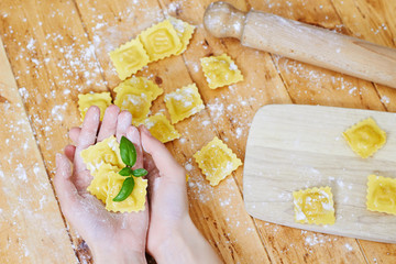 Hands holding ravioli pasta on vintage wooden table
