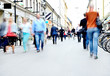 Leinwanddruck Bild - City street with motion blurred pedestrians and bicycles