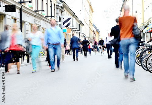 Leinwanddruck Bild City street with motion blurred pedestrians and bicycles