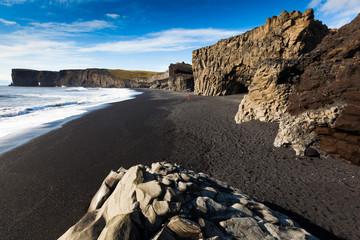 Dark sandy beach in background Dyrholaey stone, Iceland.