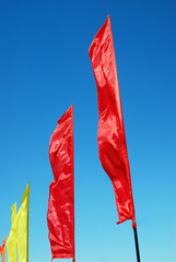 Red and yellow flags wave. Blue sky background. Taken in Moscow.