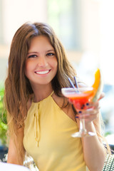 Portrait of a young woman drinking a cocktail