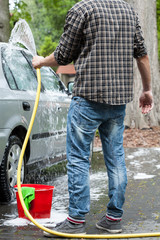 Man using garden hose for cleaning