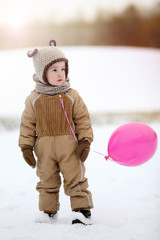 boy in a knitted hat with ears and a pink balloon on a backgroun