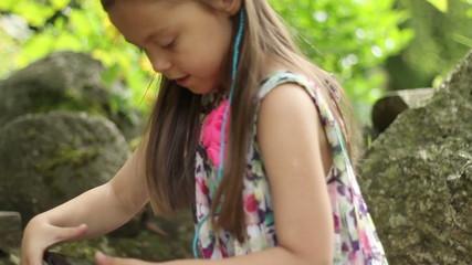 Little girl using a tablet pc in a summer garden