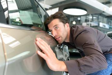 Autokauf - junger Mann testet Fahrzeug