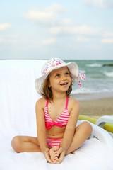 Little girl who tan on a sunbed on the beach