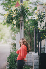 Beautiful girl in a red shirt posing on a street