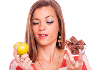 Young woman thinking what to eat first - looking on the apple