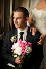 An attractive groom sitting on a chair. Hands. Hugs.