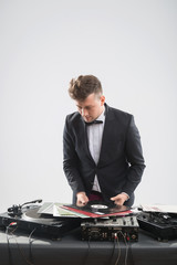 DJ in tuxedo looking at his vinyl records standing by turntable
