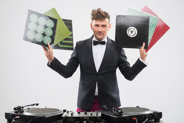 DJ in tuxedo showing his vinyl records standing by turntable