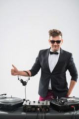 DJ in tuxedo showing his thumb up standing by turntable