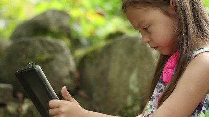Little girl using a tablet pc in a summer garden, slow motion