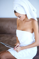 Woman Wearing Bath Towel and Using Tablet Computer