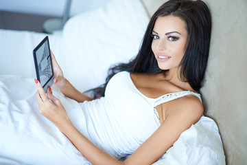 Smiling beautiful woman relaxing in bed