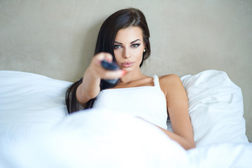 Beautiful woman lying in bed watching television