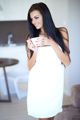 Smiling happy woman drinking a cup of coffee