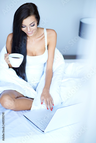 canvas print picture Young woman using a laptop in her bed