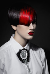 Dark portrait of pale gothic woman with creatively dyed hair