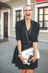 Business woman in black dress in the city with tablet