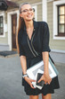 Business woman in black dress in the city with documents