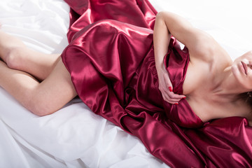 Sensual woman lying in red bedding