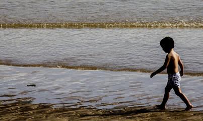 Niño paseando por la orilla de la playa