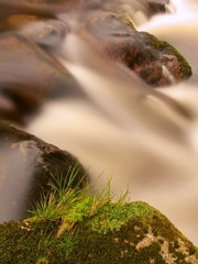 Rapid stream  with blurred waves, water run over boulders