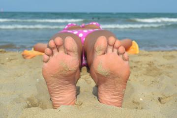 piedi insabbiati di giovane donna al mare