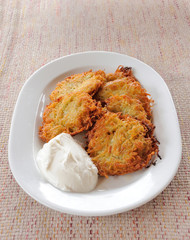 Potato pancakes with sour cream on a plate