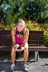 Woman sitting on a bench with smart phone before a run