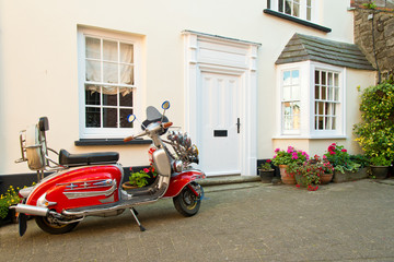 Red vintage scooter parked in front of english house